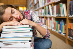 Dozing student sitting on library floor leaning on pile of books Royalty Free Stock Image
