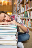 Dozing young student sitting on library floor leaning on pile of books Royalty Free Stock Image