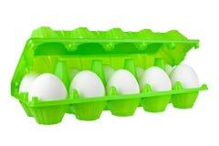Dozzina uova bianche in pacchetto di plastica verde aperto sulla fine isolata fondo bianco sulla vista laterale fotografia stock