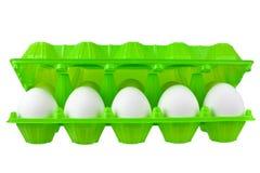 Dozzina uova bianche in pacchetto di plastica verde aperto sulla vista aperta vicina isolata fondo bianco immagini stock libere da diritti