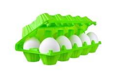 Dozzina uova bianche in pacchetto di plastica verde intenso sulla vista laterale isolata fondo bianco del primo piano fotografia stock libera da diritti