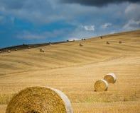 Dozzine di balle di fieno sui campi in Toscano con il cielo nuvoloso fotografie stock libere da diritti