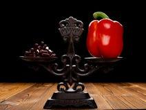 Dozzine di capsule e di peperone dolce rosso su un concetto equilibrato della scala di cibo sano e dello stile di vita alternativ fotografia stock libera da diritti