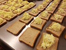 Dozzine di panini dell'insalata dell'uovo sulla tavola del metallo al ristorante dei poveri, alimentante l'affamato immagine stock libera da diritti