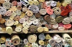 Dozzine di rotoli dei tessuti preziosi sugli scaffali immagine stock libera da diritti