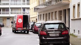 DPD parcel delivery van in central city time-lapse, fast motion. STRASBOURG, FRANCE - CIRCA 2018: DPD Delivery red van on French street with courier taking the stock video footage