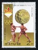 DPR COREA - CIRCA 1973: Un sello impreso en DPR Corea, juegos de las demostraciones de la olimpiada XXI que encajona a Ku Yong Jo fotos de archivo libres de regalías