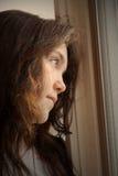 déprimé regardant à l'extérieur l'hublot Photographie stock
