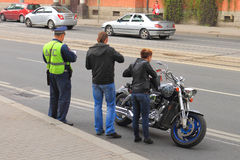 DPS officer checks the documents of a biker. KALININGRAD, RUSSIA - MAY 8, 2014: DPS officer checks the documents of a biker with a girl Royalty Free Stock Image