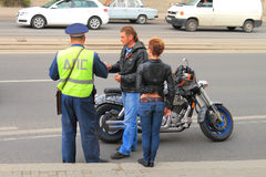 DPS officer checks the documents. KALININGRAD, RUSSIA - MAY 8, 2014: DPS officer checks the documents of a biker with a girl Stock Image