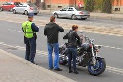 DPStjänstemannen kontrollerar dokumenten av en cyklist Royaltyfri Bild