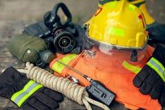 Dräkt av brandmannen som förläggas på trätabell- och naturbakgrund royaltyfri fotografi
