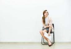 Dräkt för kvinna som i regeringsställning väntar på en stol Fotografering för Bildbyråer