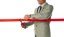 Dräkt för man som i regeringsställning klipper det röda bandet som isoleras på vit arkivbilder