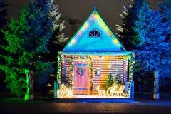 Dräkt och hemtrevligt hus nära skogen som dekoreras för vinterferierna Kulöra ljus runt om framdelen av byggnaden Nytt år och arkivfoton
