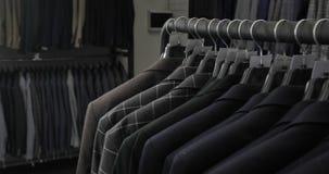 Dräkten för man` s på skräddare` s shoppar Händer för man` s väljer ett omslag i deras garderob Manligt välja lager videofilmer