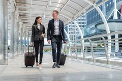 dräkten för svart för kläder för affärsmannen och affärskvinnagår samman med bagage på den offentliga gatan royaltyfri foto