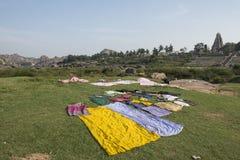 Dräkter och traditionella torkdukar som ligger i ett fält, Hampi, Indien Arkivfoton