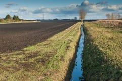 Dräneringkanal som tillsammans med kör ett plöjt fält Royaltyfria Bilder
