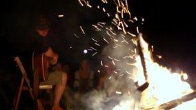 Drängen Sie das Sitzen vor einem Feuer und auf einen Musiker hören stock footage