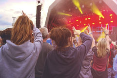 Drängen Sie sich mit den Armen in einer Luft an einem Musikfestival im Freien Stockfotos