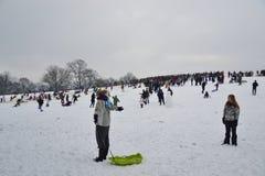 Drängen Sie sich, Schnee am Parlaments-Hügel, London genießend Stockfoto