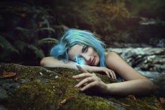 Dríada del bosque observando una mariposa mágica imagenes de archivo