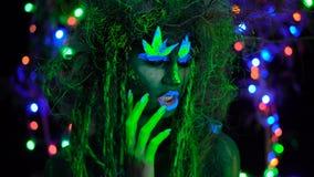 Dríade verde místico ansioso irritado na luz preta do fluor UV com as árvores de incandescência no fundo filme