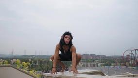 Drôle idiot temporaire d'homme adulte dans le masque de singe avec le paysage urbain au fond dans le mouvement lent clips vidéos