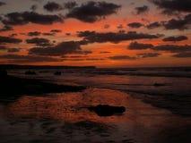 dröja sig kvar solnedgång för strand Arkivbild