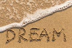 Dröm - inskrift på sandstranden Arkivbild