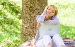 Dröm om ny jobb eller förflyttning Flickabärbara datorn som in drömmer, parkerar sitter på gräs Dröm om lyckat projekt Kvinna fotografering för bildbyråer