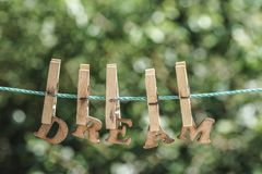 DRÖM- ord som är skriftligt vid hängda träbokstäver på rep på trädgården Fotografering för Bildbyråer
