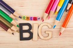 DRÖM- STORT ord och färgrika blyertspennor på träskrivbordet arkivbild