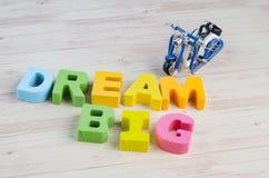 DRÖM- STORT ord på blå bakgrund för träskrivbord arkivfoto