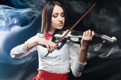 Drömlik kvinna som spelar fiolen på en svart bakgrund Arkivfoto