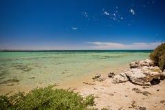 Drömlik lös strand och hav under en blå himmel royaltyfri fotografi