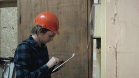 Drömlik le repairman som håller minnestavlan i gammal byggnad, provelektriker stock video