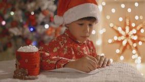 Drömlik pojke i pyjamas och den santa hatten som skrivar brevet till jultomten med koppen av kakao med marshmallowen stock video