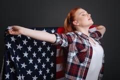 Drömlik säker kvinna som visar hennes patriotiska ande Royaltyfri Foto
