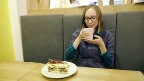 Drömlik ung flicka i exponeringsglas som dricker varmt scandinavian te med blåbär och mintkaramellen från en rosa kopp och in kop arkivfilmer