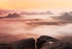 Drömlikt dimmigt landskap Det majestätiska berget klippte belysningmisten som den djupa dalen är full av färgrik dimma, och steni Arkivbilder