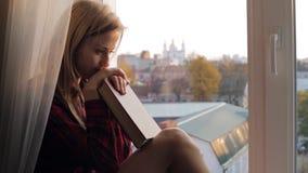 Drömma den unga kvinnan med boksammanträde på en fönsterbräda hemma stock video
