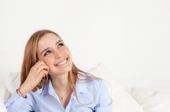 Drömma den unga kvinnan på en soffa Royaltyfri Foto
