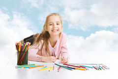 Drömma för flicka som söker efter teckningsidé. Le blå himmel för barn royaltyfria bilder