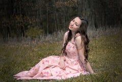 Drömma flickan som sitter på gräset Royaltyfri Bild