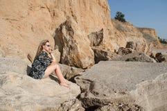 Drömma härligt flickasammanträde på stora stenar Royaltyfri Fotografi