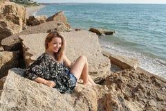 Drömma härligt flickasammanträde på stora stenar Royaltyfri Foto