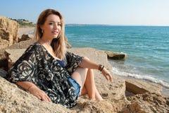 Drömma härligt flickasammanträde på stora stenar fotografering för bildbyråer