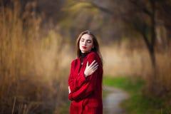 drömma kvinnabarn Den härliga kvinnlign med långt sunt hår som tycker om naturen parkerar in, den bärande röda koftan Vår royaltyfria foton